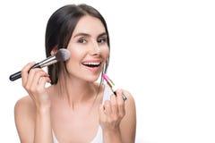 Glad girl doing facial make-up Stock Photo
