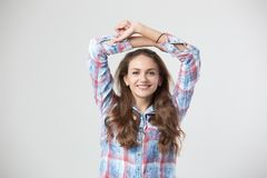 Glad girl dressed in a checkered shirt keeps her hands over the head on the white background in the studio stock photo
