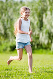 Glad girl in elementary school age running on grass. Glad small smiling girl in elementary school age running on green grass in park royalty free stock images