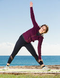 Glad girl exercising on exercise mat Stock Photography