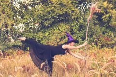 Glad girl in witch costume doing fitness Royalty Free Stock Photo