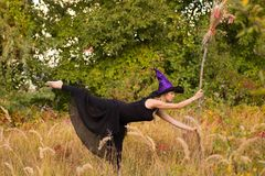 Glad girl in witch costume doing fitness Stock Photos