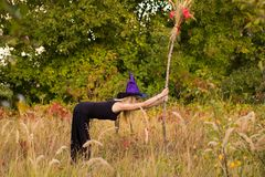 Glad girl in witch costume practicing yoga Stock Photos