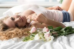 Merry young woman resting in bedding. Glad girl is lying on bed and looking at camera with affable smile. She holding flower. Portrait Stock Image