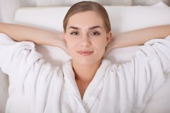 Glad girl lying on comfortable deckchair at beauty center. Life is wonderful. Top view portrait of dreamful young woman relaxing on daybed at spa lounge. She is Royalty Free Stock Photography