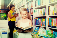 Glad girl in school age looking in open chosen book Stock Image