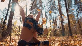 Glad girl is sitting crossed legs on ground in park and tossing leaves up. Joyous woman is resting in autumn forest, sitting on ground and throwing foliage. She stock video footage