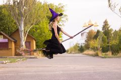 Glad girl in witch costume flies on broomstick Stock Images