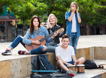 Glad girls and boys with musical instruments. Glad girls and boys teenagers friends with musical instruments together outdoors Royalty Free Stock Images