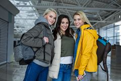 Glad girls posing at the airport with rucksacks. Portrait of female company standing at the airport with backpacks, looking at camera and smiling Royalty Free Stock Photos