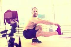 Glad gladlynt sportig man som hemma gör övningar royaltyfri fotografi