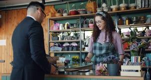 Glad grabb som betalar för blommor i lager genom att använda kreditkorten som talar till blomsterhandlaren arkivfilmer