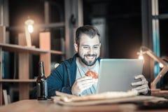 Glad IT-grabb som slukar pizza royaltyfria bilder