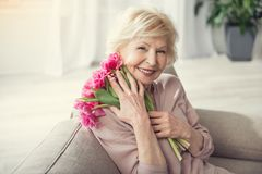 Glad granny holding close bouquet. Portrait of old woman relaxing on cozy sofa with bunch of flowers in hug. She is looking at camera with happiness Stock Photography