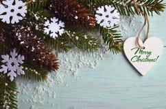 glad greeting för kortjul Dekorativa snöflingor, grankottar, hjärta och snöig granträdfilial på ljus - blå bakgrund Arkivfoton