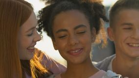 Glad group of multiethnic teens happily smiling on camera, strong friendship