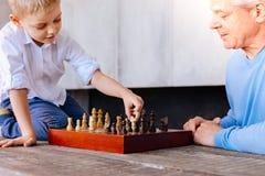 Glad gullig pojke som rymmer ett schackstycke Royaltyfria Foton