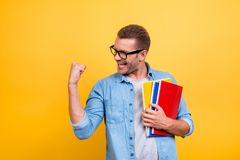 Glad guy raising his hand with fist having good mood celebrating. Victory, passes exams, completed work, holding three colorful copy books standing over yellow Royalty Free Stock Photography