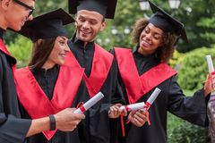 Joyful young students showing their diplomas in graduation clothing royalty free stock photography