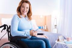 Glad handikappad kvinna som använder hennes telefon Arkivbilder