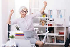 Glad happy business lady expressing joy at the workplace Stock Photography