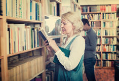 Glad happy woman reading book in book shop Royalty Free Stock Photography
