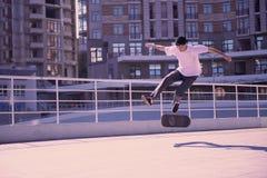 Glad idrottsman som tycker om aktiviteter med adrenalin på skateboarden arkivfoton
