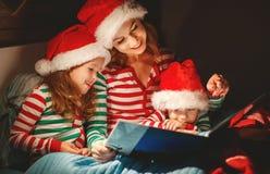Glad jul! familjmodern läser till barnboken för säng arkivfoton
