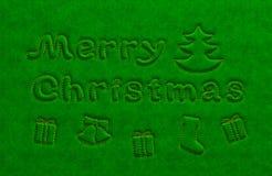 Glad jul guld- text och attribut på grön sammet ytbehandlar Arkivbilder