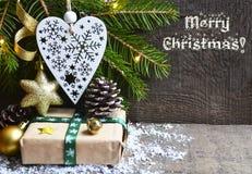 glad jul Julgarnering med granträdet, gåvaasken, hjärta för vit jul och sörjer kottar på gammal träbakgrund Arkivfoto