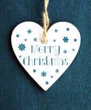 glad jul Julgarnering med vit trähjärta på blå filtbakgrund Arkivfoto