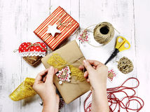 Glad jul - kvinnan räcker inpackning av av gåvaasken och garneringar Fotografering för Bildbyråer
