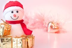 Glad jul, nytt år, snögubbegåvor i guld- askar och en guld- hjärta på en bakgrund av rosa och gul bokeh royaltyfri foto