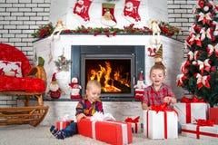 Glad jul och lyckliga ferier! Barn öppnar gåvor från Santa Claus kommer riktiga drömmar royaltyfria foton