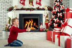 Glad jul och lyckliga ferier! Det gulliga barnet grundar många gåvor under julgranen arkivfoton