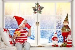 Glad jul och lyckliga ferier! Ett småbarn som sitter på fönstret som äter kakor och dricker, mjölkar royaltyfri foto