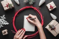 Glad jul och lyckliga ferier! Kvinnahänder med ljust rött spikar handstilbokstaven med silverpennan Royaltyfri Bild