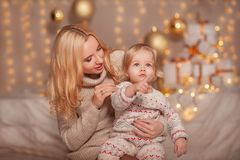 Glad jul och lyckliga ferier! Liten ungeflicka med mammasammanträde i dekorerat rum med gåvor och ljus och att tycka om dotter Arkivbilder