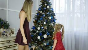 Glad jul och lyckliga ferier! Mamman och dottern dekorerar julgranen inomhus Morgonen för Xmas stock video