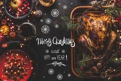 Glad jul och lyckliga nya året som hälsar textbokstäver på julmatställetabellen med den hela grillade kalkon, tjänade som med sås arkivfoton
