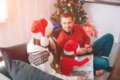 Glad jul och lyckligt nytt år Älskvärd bild av familjen som tillsammans sitter på soffan Förälderblick på de Kvinna royaltyfri bild