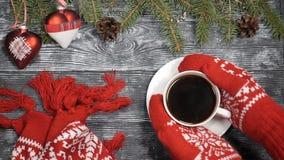 Glad jul och lyckligt nytt år 2019 2020 begrepp Händer i röda stack tumvanten tar en kopp av varmt kaffe av ett trä stock video
