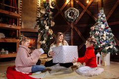 Glad jul och lyckligt nytt år Gladlynt mamma och hennes gulliga dotter och son som utbyter gåvor Förälder och barn royaltyfri foto