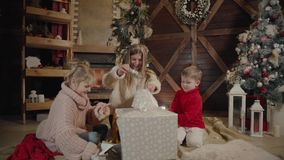 Glad jul och lyckligt nytt år Gladlynt mamma och hennes gulliga dotter och son som utbyter gåvor Förälder och barn arkivfilmer