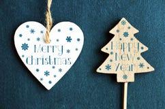 Glad jul och lyckligt nytt år Julgarnering med den vita trähjärta- och granträdstatyetten på blå filtbakgrund Royaltyfria Bilder