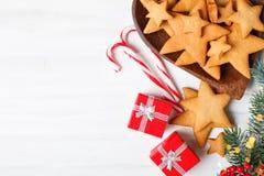 Glad jul och lyckligt nytt år Kakor, gåvor och gran-träd filialer på en vit trätabell Selektivt fokusera arkivfoton