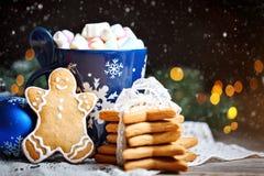 Glad jul och lyckligt nytt år Koppkakao, kakor, gåvor och gran-träd filialer på en trätabell Selektivt fokusera arkivfoto