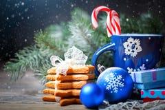 Glad jul och lyckligt nytt år Koppkakao, kakor, gåvor och gran-träd filialer på en trätabell Selektivt fokusera arkivbild