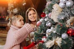 Glad jul och lyckligt nytt år Mamman och dottern dekorerar julgranen inomhus Älska upp familjslut royaltyfria bilder