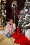 Glad jul och lyckligt nytt år Mamman och dottern dekorerar julgranen inomhus Älska upp familjslut royaltyfria foton